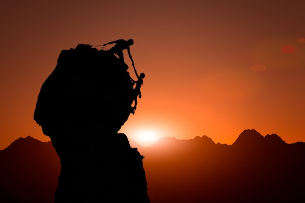 Zespół wspinaczy pomaga podbić szczyt o zachodzie słońca