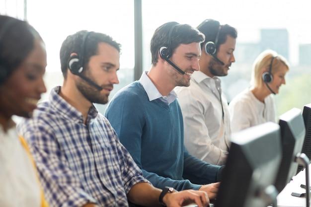 Zespół współpracowników pracujących przy biurku z zestawu słuchawkowego