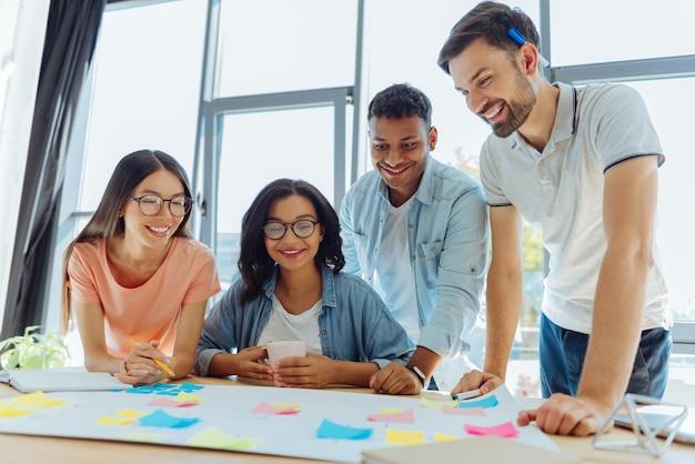 Zespół współpracujący. szczęśliwi, sympatyczni młodzi ludzie patrząc na swój plakat i omawiając swój projekt podczas wspólnej pracy