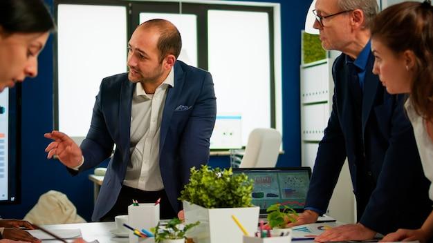 Zespół zróżnicowanego startupowego kolegi przedsiębiorcy, który spotyka się w profesjonalnym broadroomie w miejscu pracy, dzieli się pomysłami i pomysłami na zarządzanie strategią finansową. wielorasowe planowanie ludzi biznesu.