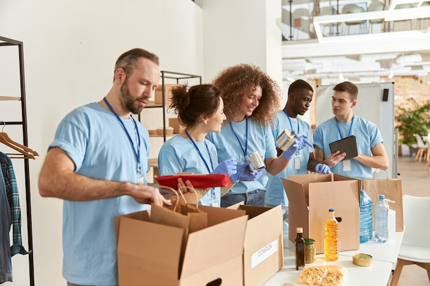 Zespół zróżnicowanych wolontariuszy w rękawicach ochronnych sortujących żywność w kartonach