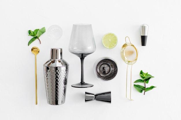 Zestaw akcesoriów barowych do przygotowywania koktajli. shaker, jigger, szkło, łyżka i inne narzędzia barowe z liśćmi limonki i mięty na witkowym tle.