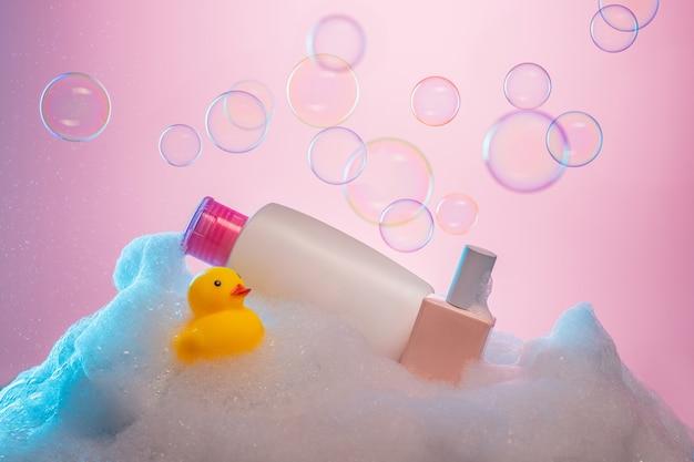 Zestaw akcesoriów do kąpieli na tle mydlanym. żółta gumowa kaczka i żel pod prysznic w butelkach.