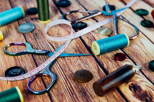 Zestaw akcesoriów do szycia, takich jak szpule kolorowej nici, guziki, taśma miernicza, nożyczki vintage i igły do szycia na drewnianym tle