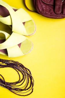 Zestaw akcesoriów kobiecych rzeczy na sezon letni. brązowe torby żółte sandały na platformie, naszyjnik. flat lay.