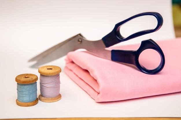 Zestaw akcesoriów krawieckich. zamknij się na stosie złożonej różowej tkaniny, nożyczki do szycia i szpule nici