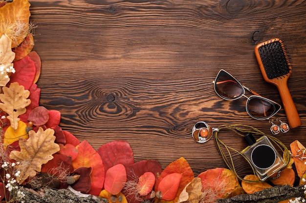 Zestaw akcesoriów mody kobiet. jesienne liście, okulary przeciwsłoneczne, perfumy i biżuteria