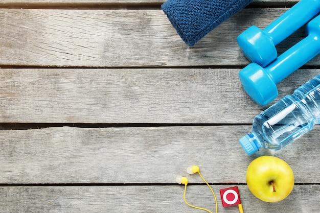 Zestaw akcesoriów sportowych do fitnessu ze sprzętem do ćwiczeń na szary drewniany.