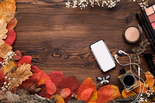 Zestaw akcesoriów żeńskich. jesienne liście, smartfon i słuchawki na drewno