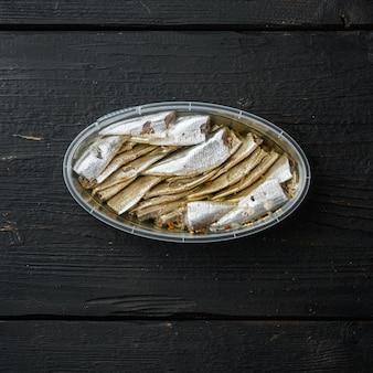 Zestaw anchois w puszkach, w plastikowym pojemniku, na czarnym drewnianym stole, widok z góry płasko leżący, format kwadratowy