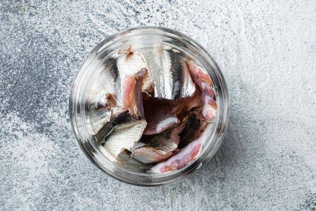 Zestaw anchois w puszkach, w szklanym słoju, na szarym tle