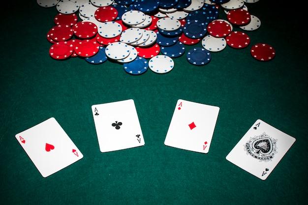Zestaw asów kart do gry i żetony na zielonym stole pokerowym