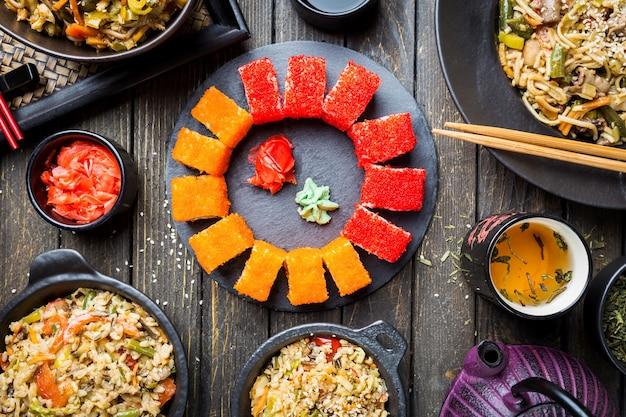 Zestaw azjatyckich dań serwowany na czarnym drewnianym stole. kuchnia chińska, japońska i wietnamska, sushi, ryż i makaron.