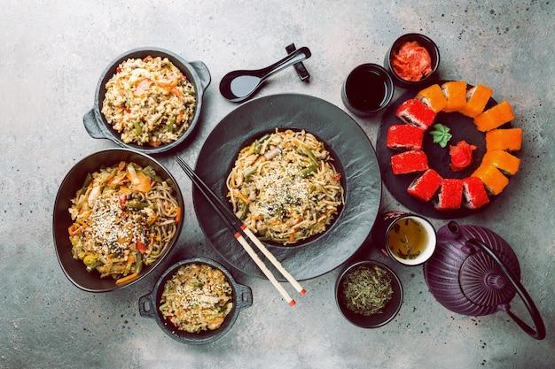 Zestaw azjatyckich dań serwowany na szarym kamieniu. kuchnia chińska, japońska i wietnamska, sushi, ryż i makaron.