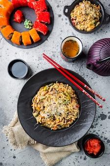 Zestaw azjatyckich potraw podawany na szarym kamieniu. kuchnia chińska, japońska i wietnamska, sushi, ryż i makaron.