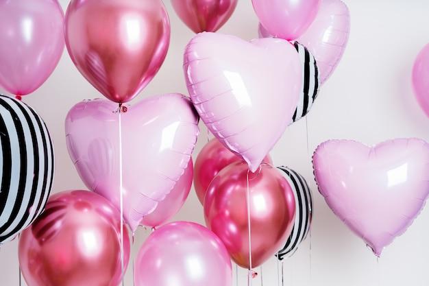 Zestaw balonów w formie serca i okrągłe różowe i paski na jasnym tle z miejsca kopiowania.