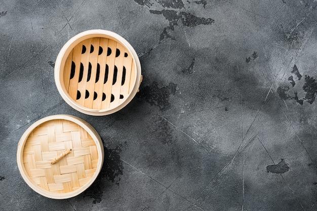 Zestaw bambusowego parowca, z kopią miejsca na tekst lub jedzenie, z kopią miejsca na tekst lub jedzenie, widok z góry płaski, na szarym tle kamiennego stołu