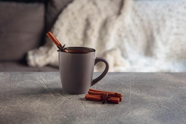 Zestaw białej herbaty i ciasta na drewnianym stole w kolorze szarym. biała drewniana taca z filiżankami, czajnikiem i girlandą oświetleniową.