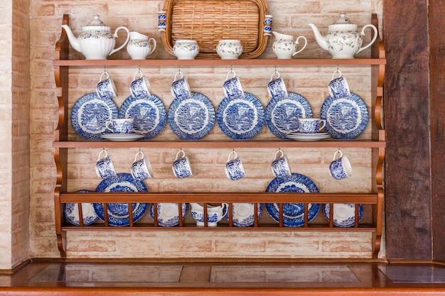 Zestaw biało-niebieskich naczyń dobrze zorganizowany w drewniane meble w ceglanej tylnej ścianie