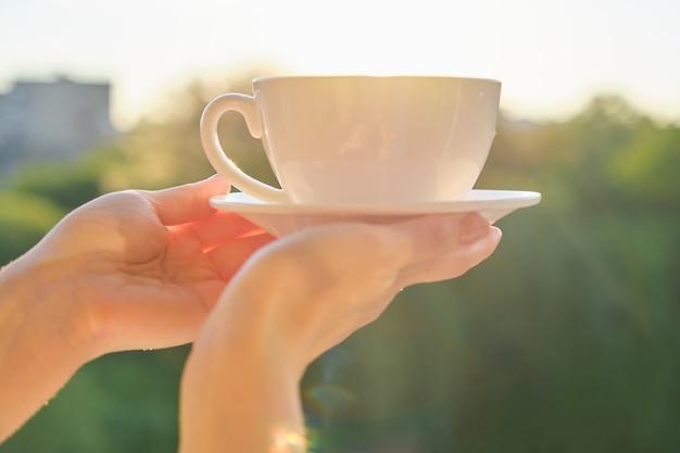 Zestaw biały ceramiczny kubek ze spodkiem w ręce kobiety, tło zachód słońca