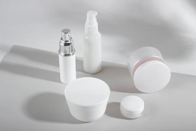 Zestaw białych butelek kosmetycznych i słoiczków z twardymi cieniami.