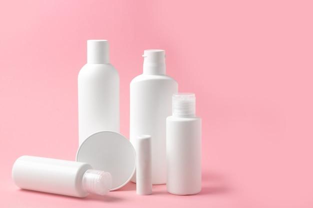 Zestaw białych butelek kosmetycznych i słoików na różowym tle z miejscem na dodanie tekstu