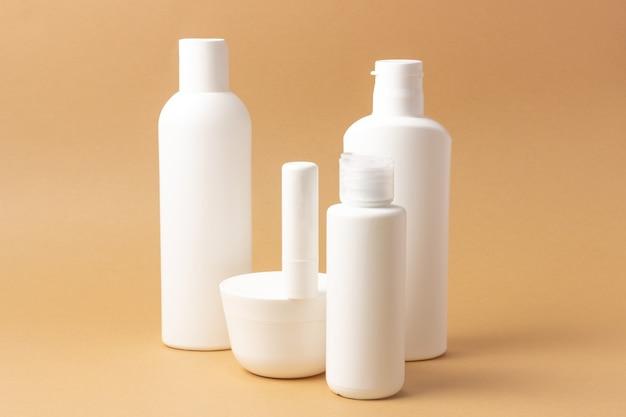 Zestaw białych butelek kosmetycznych i słoików z miejscem na dodanie tekstu