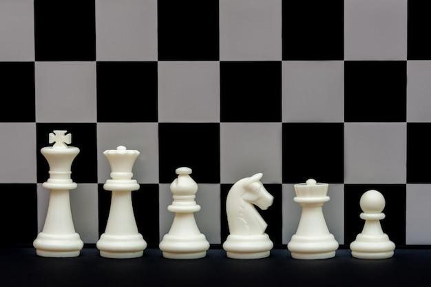 Zestaw białych figur szachowych na tle szachownicy gra w szachy