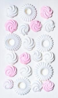 Zestaw białych i różowych ciasteczek ptasie mleczko i beza na białej ścianie, widok z góry.