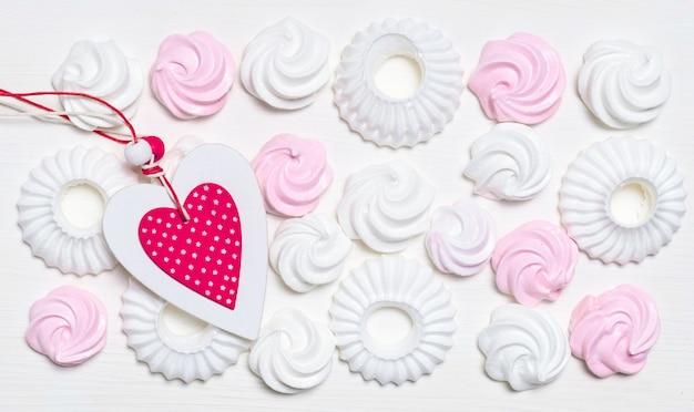 Zestaw białych i różowych ciasteczek ptasie mleczko i beza z różowym sercem na białej ścianie, widok z góry.