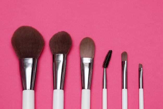 Zestaw białych pędzli do makijażu na różowym tle