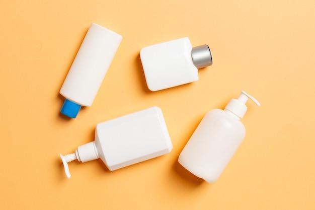 Zestaw białych pojemników kosmetycznych na białym tle na kolorowej powierzchni, widok z góry z miejsca na kopię