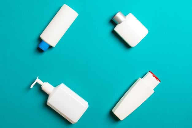 Zestaw białych pojemników kosmetycznych na białym tle na kolorowym tle, widok z góry z miejsca na kopię. grupa plastikowych pojemników na butelki do pielęgnacji ciała z pustą przestrzenią do projektowania.