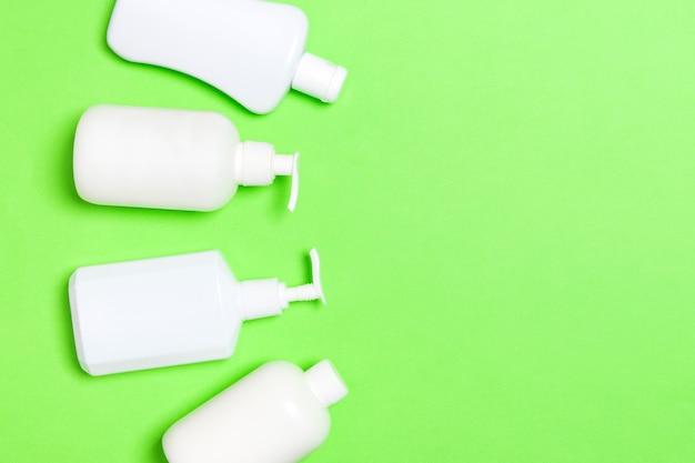 Zestaw białych pojemników kosmetycznych na białym tle na zielonej powierzchni, widok z góry z miejsca na kopię