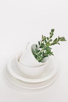 Zestaw białych talerzy z trzech talerzy i kubek ozdobiony gałązką eukaliptusa