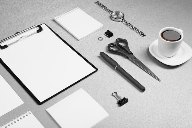 Zestaw biurowy z białymi kartkami papieru, filiżanką kawy, zegarkiem i papeterią