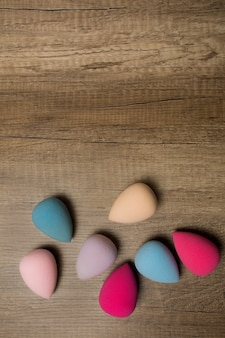Zestaw blenderów kosmetycznych na tle drewna. miejsce na tekst