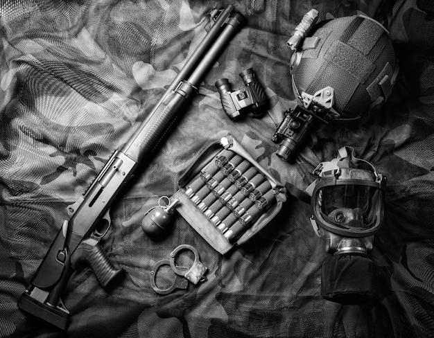 Zestaw broni myśliwca jednostki specjalnej. strzelba, amunicja, granat, kajdanki i maska przeciwgazowa. widok z góry. różne środki przekazu