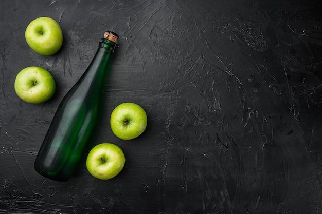 Zestaw butelek cydru jabłkowego, na czarnym tle ciemnego kamiennego stołu, widok z góry płasko leżący, z miejscem na kopię tekstu