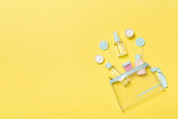 Zestaw butelek kosmetycznych rozmiar podróży na żółtym tle. płaskie układanie kremowych słoików. widok z góry koncepcji stylu bodycare
