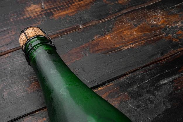 Zestaw butelek zielonego wina, na starym ciemnym tle drewnianego stołu, z kopią miejsca na tekst