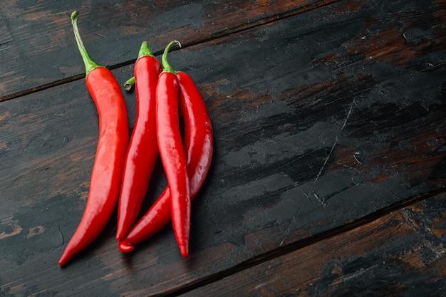 Zestaw całej czerwonej papryki chili, na starym drewnianym stole