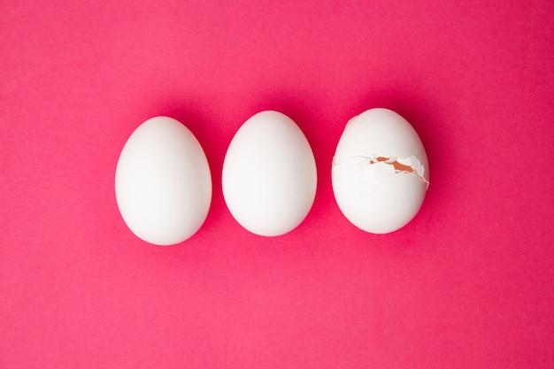 Zestaw całych i pękniętych jajek na różowej powierzchni