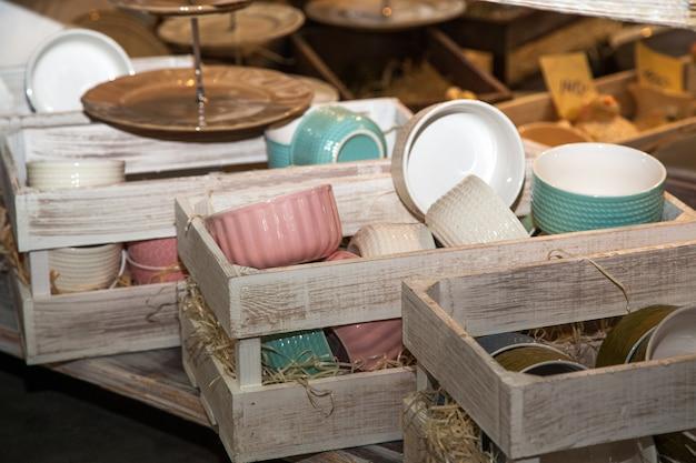 Zestaw ceramicznych zastaw stołowych w drewnianych skrzynkach w kuchni