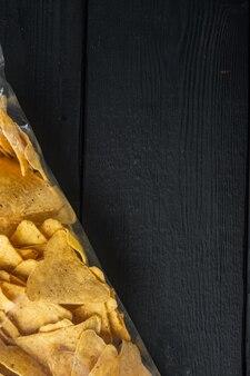 Zestaw chipsów kukurydzianych, na czarnym drewnianym stole, widok z góry lub płasko ułożony