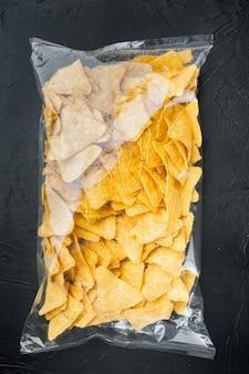 Zestaw chipsów kukurydzianych, na czarnym stole, widok z góry lub płasko