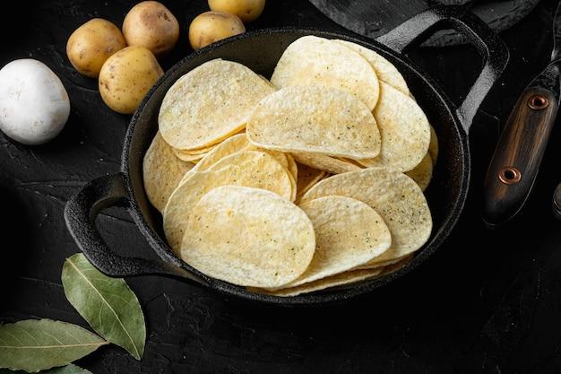 Zestaw chipsów ziemniaczanych, na czarnym tle kamienia
