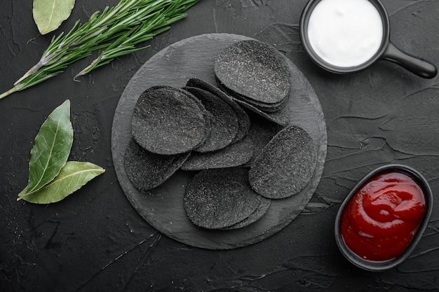 Zestaw chipsów ziemniaczanych z serem i szczypiorkiem, na stole z czarnego kamienia, widok z góry na płasko