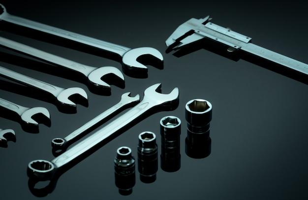 Zestaw chromowanych kluczy lub kluczy, nasadki sześciokątnej i suwmiarki na ciemnym stole w warsztacie