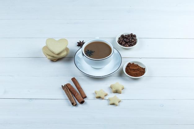 Zestaw ciasteczek, przypraw, ziaren kawy, zmielonej kawy i kawy w filiżance na podłoże drewniane. widok pod dużym kątem.